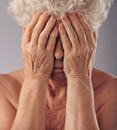 Elderly woman covering her face with hands