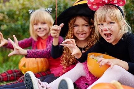 Young girls with Halloween treats in plastic pumpkins