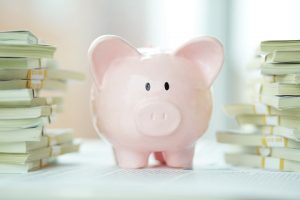 Piggy bank with stacks of money - care fees saved by Clarity Care Consulting being successful with CHC application